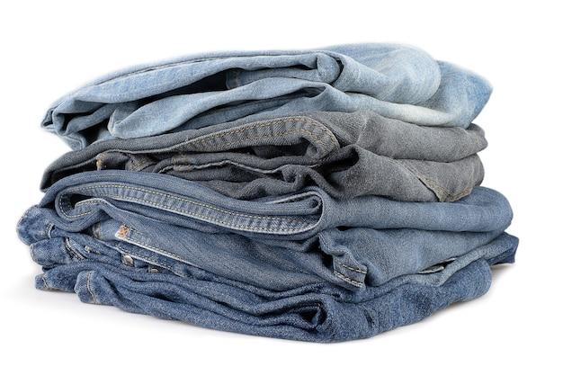 Stapel verschiedener jeanshosen auf weiß