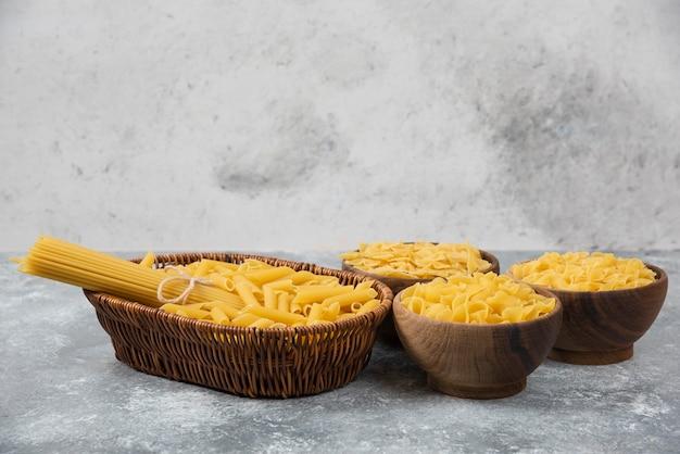 Stapel verschiedener ungekochter trockener nudeln in weidenkorb und holzschalen.