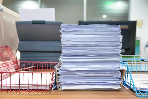 Stapel vieler papierdokumente auf schreibtischbüro kommen voran
