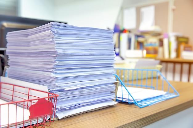 Stapel vieler papierdokumente auf schreibtischbüro kommen voran.