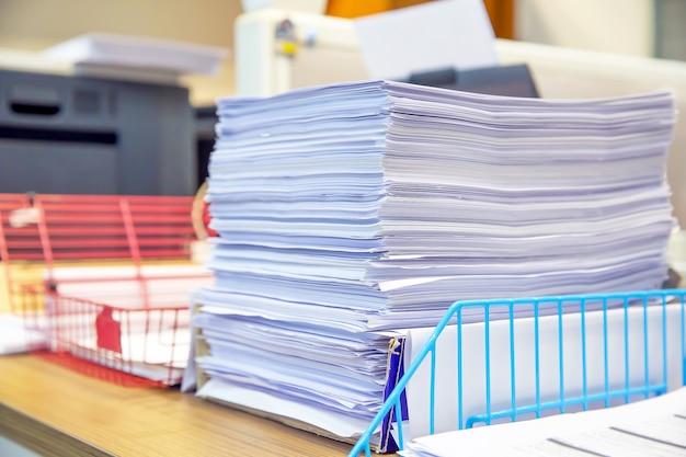 Stapel vieler papiere auf schreibtischbüro kommen voran.