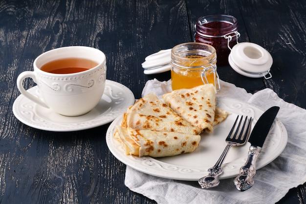 Stapel von amerikanischen pfannkuchen oder krapfen mit erdbeer- und blaubeermarmelade in der weißen platte auf hölzernem rustikalem tisch