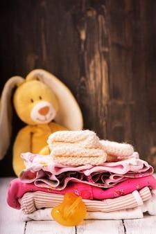 Stapel von babykleidung für neugeborene