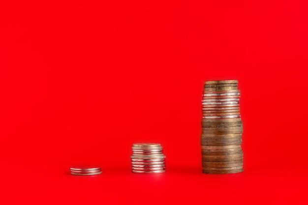 Stapel von bargeldmünzen mit zunahmediagramm auf der farboberfläche