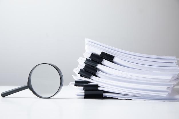 Stapel von berichtspapierdokumenten mit lupe. geschäftskonzept und suche.