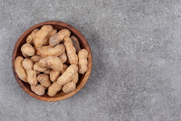 Stapel von bio-erdnüssen in holzschale