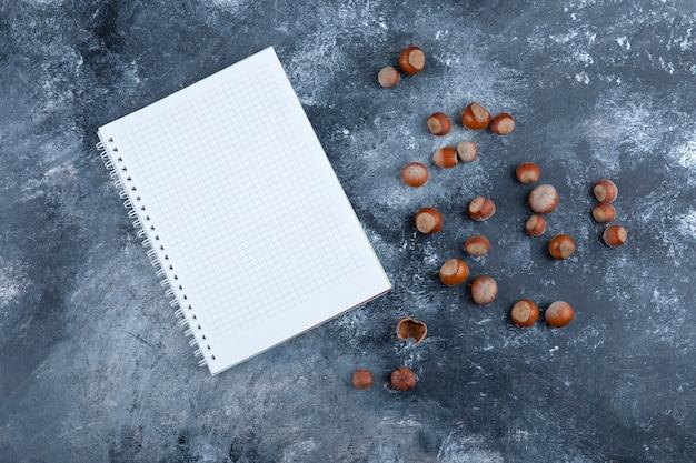Stapel von bio-geschälten haselnüssen mit leerem notizbuch auf marmor.