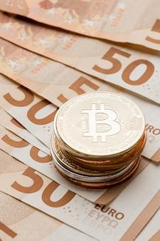 Stapel von bitcoins auf banknotenanordnung