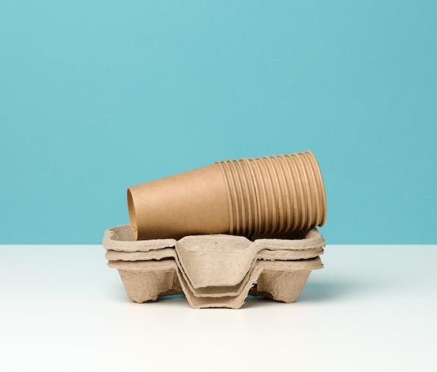 Stapel von braunen einwegbechern aus papier und stehen auf weißem tisch, blauer hintergrund
