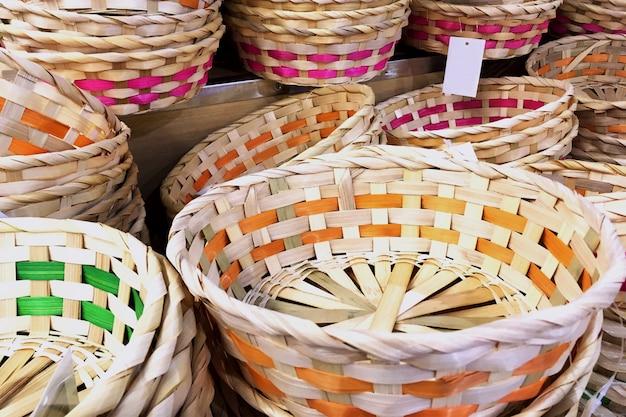 Stapel von braunen weidenkörben verschiedenen formen von der rebe auf dem markt.