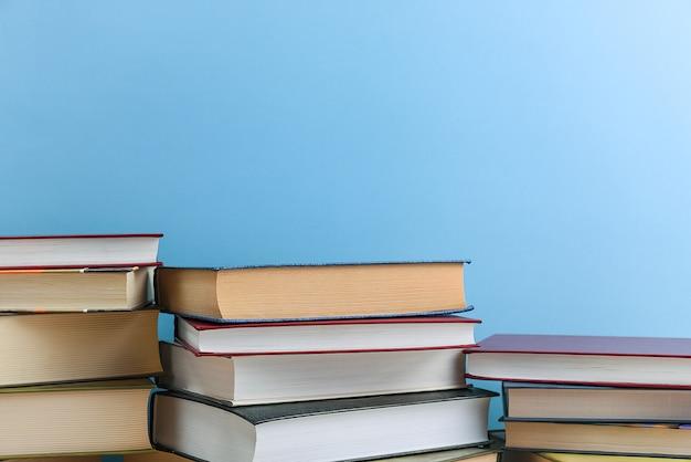 Stapel von büchern mehrere auf einem blauen hintergrund nahaufnahme. zurück in die schule, bildung, lernen,