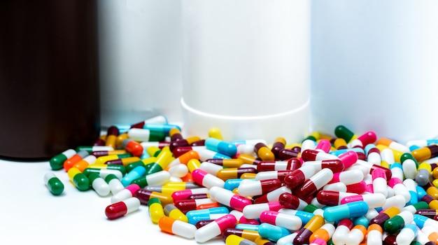 Stapel von bunten antibiotika-kapselpillen auf unscharfer plastikdrogenflasche. antibiotikaresistenz. pharmaindustrie.