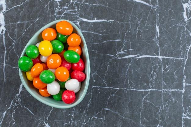 Stapel von bunten bonbons in der blauen schüssel