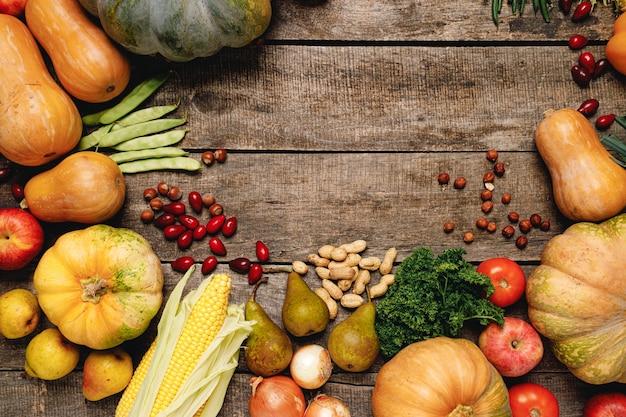 Stapel von bunten früchten und gemüse auf hölzernem hintergrund