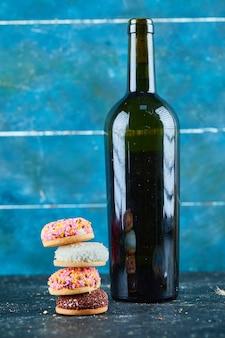 Stapel von bunten geschwollenen keksen mit einer flasche wein auf blauer wand.