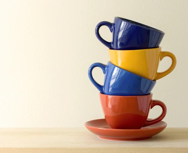 Stapel von bunten kaffeetassen auf dem tisch