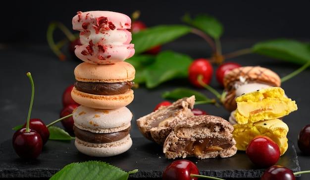 Stapel von bunten macarons und reifen roten kirschen auf schwarzem holzhintergrund, nahaufnahme