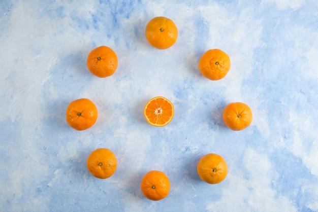 Stapel von clementinen-mandarinen auf blauer oberfläche