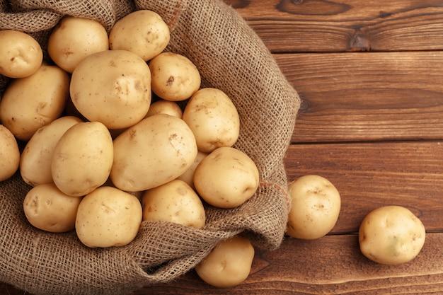 Stapel von den kartoffeln, die auf hölzernen brettern liegen