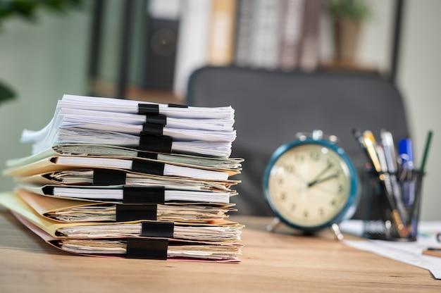 Stapel von dokumenten mit büroklammerordner auf einem geschäftstisch in einem geschäftsbüro.