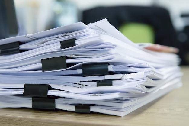 Stapel von dokumenten mit schwarzen clips auf dem schreibtisch stapeln sich