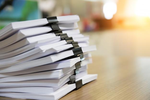 Stapel von dokumenten mit schwarzen clips auf dem schreibtisch