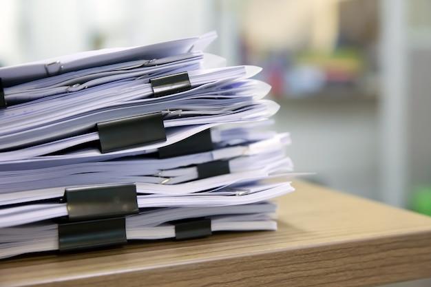 Stapel von dokumenten stapeln sich auf dem tisch.