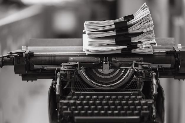 Stapel von dokumenten tempo auf vintage-schreibmaschine