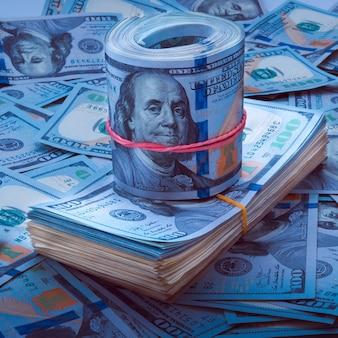 Stapel von dollar, die rolle von dollar auf dem hintergrund von hundert dollarscheinen.