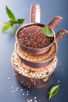 Stapel von drei kupfernen messbechern mit gemischter roher quinoa