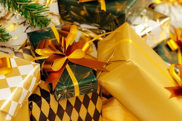 Stapel von eingewickelten grün- und goldgeschenken für weihnachten