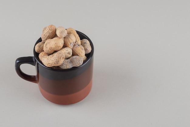 Stapel von erdnüssen in einem becher auf marmorhintergrund.