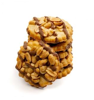 Stapel von erdnussbutterkeksen mit dunkler schokolade lokalisiert auf weißem hintergrund. frische hausgemachte nussige cracker nahaufnahme