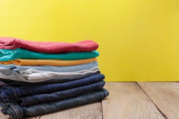 Stapel von farbiger kleidung auf hölzernem tabellengelbhintergrund