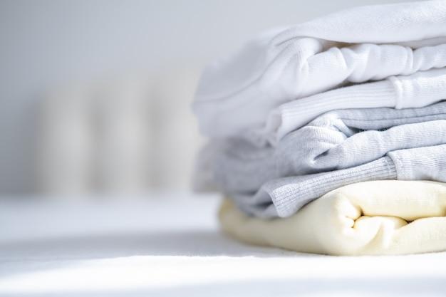 Stapel von frauen bunte sweatshirts, kapuzenpullis in pastellfarben auf weißem bett. saisonale einkäufe, wäscherei, urlaubskonzept.