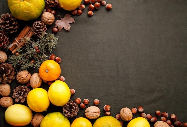 Stapel von frischen früchten, von kegeln und von nüssen auf dem dunkelgrünen gewebe