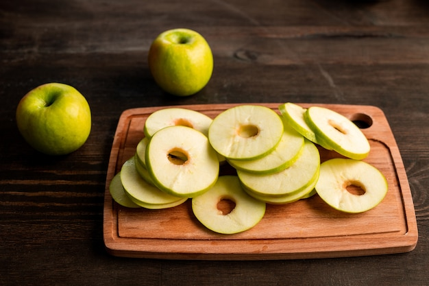 Stapel von frischen grünen äpfeln bereit, auf obsttrockner auf holzschneidebrett und zwei oma-schmiede in der nähe auf küchentisch gelegt zu werden