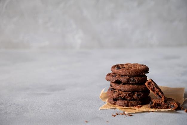 Stapel von frischen hausgemachten knusprigen keksen mit dunkler schokolade. auf einem grauen hintergrund. speicherplatz kopieren