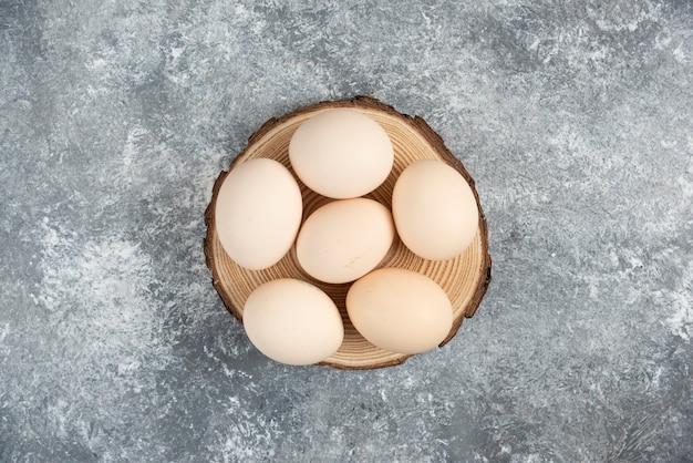 Stapel von frischen ungekochten bio-eiern auf holzstück gelegt.