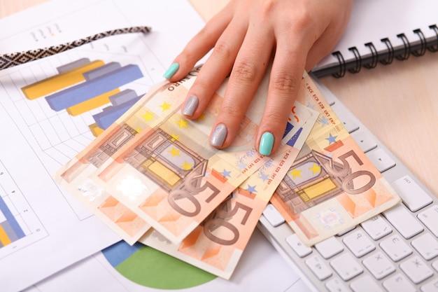 Stapel von fünfzig eurobanknoten in den frauenhänden - nahaufnahme