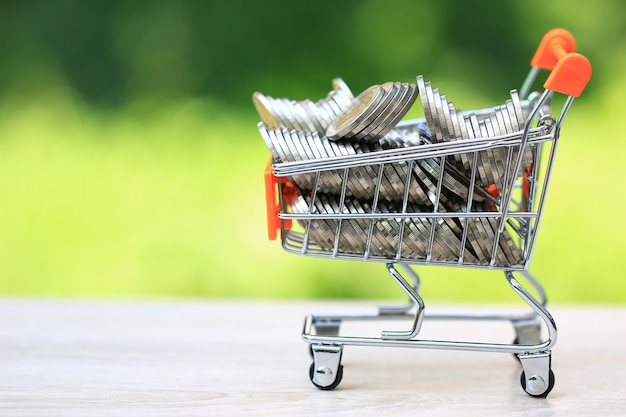 Stapel von geldmünzen im mini-einkaufswagen auf natürlichem grünem hintergrund, wachstum der geschäftsinvestitionen und geld sparen für die vorbereitung im zukünftigen konzept