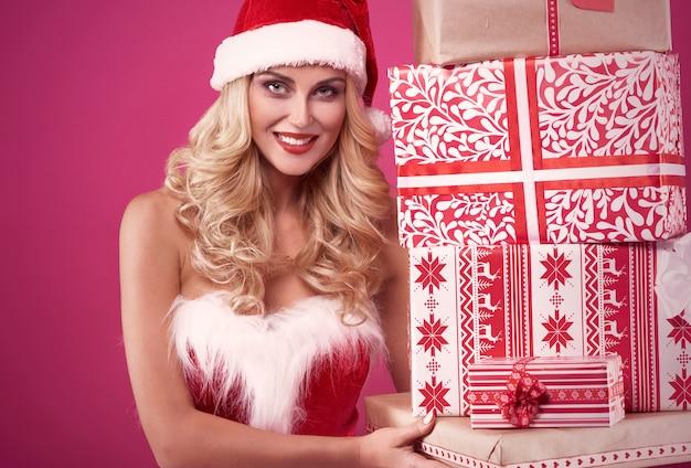 Stapel von geschenken, die vom sexy weihnachtsmann gehalten werden
