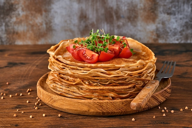 Stapel von glutenfreien buchweizenmehl-crepes-pfannkuchen mit kirschtomaten und rucola-mikrogrün auf holzplatte, hausgemachtes gesundes backen zum frühstück.