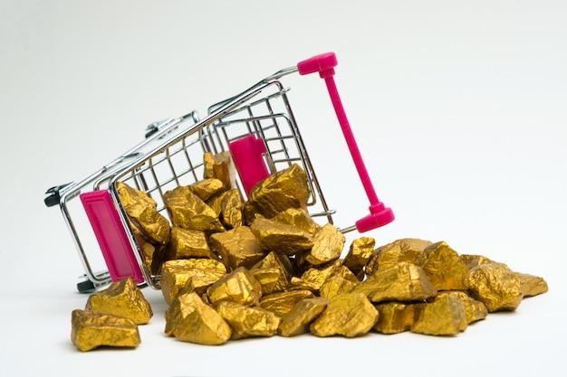 Stapel von goldnuggets oder golderz in der warenkorblaufkatze auf weißem hintergrund