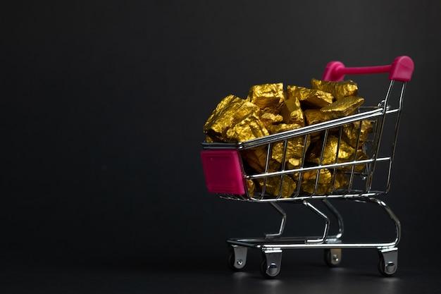 Stapel von goldnuggets oder von golderz im einkaufswagen oder in der supermarktlaufkatze auf schwarzem hintergrund