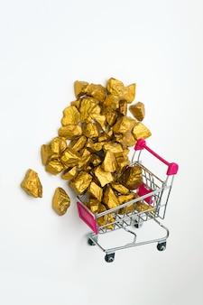 Stapel von goldnuggets oder von golderz im warenkorb oder in der supermarktlaufkatze auf weißem hintergrund, edelstein oder klumpen des goldenen steins