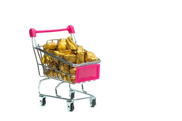 Stapel von goldnuggets oder von golderz im warenkorb oder in der supermarktlaufkatze
