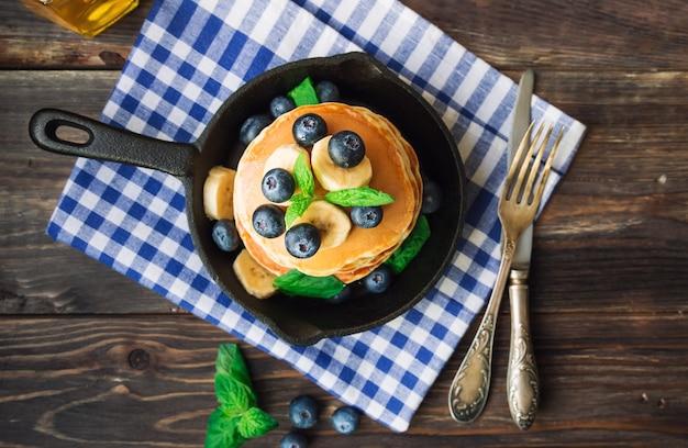 Stapel von hausgemachten pfannkuchen in eisenpfanne mit blaubeerbananen- und minzblättern auf rustikalem hölzernem hintergrund draufsicht
