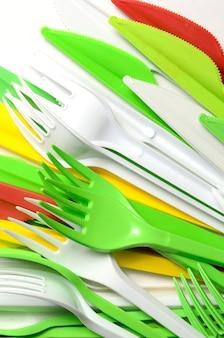 Stapel von hellen gelben, grünen und weißen plastikküchengeschirreinweggeräten