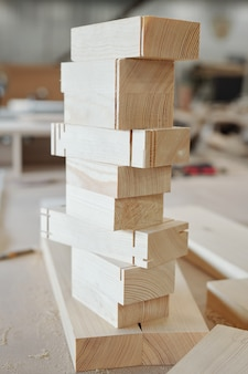 Stapel von hölzernen ziegelwerkstücken, die bereit sind, zur herstellung von möbeln verwendet zu werden, die auf werkbank des modernen fabrikarbeiters stehen